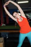 Ritratto dell'atleta femminile che allunga con le armi alzate Immagini Stock