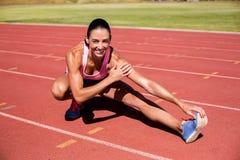Ritratto dell'atleta femminile che allunga il suo tendine del ginocchio Fotografia Stock Libera da Diritti