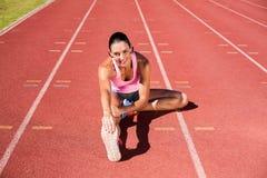Ritratto dell'atleta femminile che allunga il suo tendine del ginocchio Immagine Stock