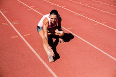 Ritratto dell'atleta femminile che allunga il suo tendine del ginocchio Fotografia Stock