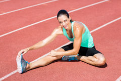 Ritratto dell'atleta femminile che allunga il suo tendine del ginocchio Fotografie Stock Libere da Diritti