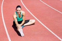 Ritratto dell'atleta femminile che allunga il suo tendine del ginocchio Fotografie Stock