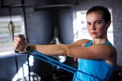 Ritratto dell'atleta femminile che allunga la banda di resistenza Immagini Stock Libere da Diritti