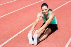 Ritratto dell'atleta femminile che fa allungando esercizio Immagine Stock