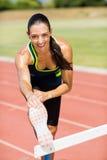 Ritratto dell'atleta femminile che si scalda sopra la transenna Fotografia Stock Libera da Diritti