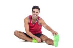 Ritratto dell'atleta maschio che allunga il suo tendine del ginocchio Fotografia Stock Libera da Diritti