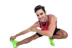 Ritratto dell'atleta maschio che allunga il suo tendine del ginocchio Immagine Stock