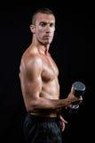 Ritratto dell'atleta senza camicia sicuro che risolve con la testa di legno Immagine Stock