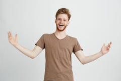 Ritratto dell'esultanza di risata positiva allegra felice del giovane che gesturing esaminando macchina fotografica sopra fondo b Immagini Stock Libere da Diritti