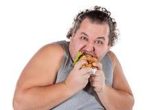 Ritratto dell'hamburger mangiatore di uomini grasso divertente degli alimenti a rapida preparazione isolato su fondo bianco fotografie stock