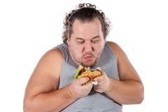 Ritratto dell'hamburger mangiatore di uomini grasso divertente degli alimenti a rapida preparazione isolato su fondo bianco fotografia stock libera da diritti