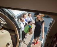 Ritratto dell'imbarco di Rich Woman With Shopping Bags Fotografie Stock