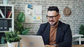 Ritratto dell'imprenditore attraente che per mezzo del computer portatile poi che esamina sorridere della macchina fotografica video d archivio