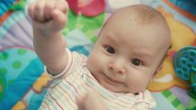 Ritratto dell'infante che esamina macchina fotografica sulla stuoia colorata Chiuda su del fronte sveglio del bambino stock footage