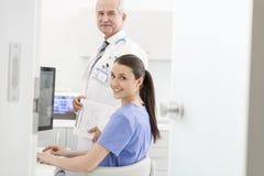 Ritratto dell'infermiere facendo uso del computer portatile allo scrittorio con medico senior in clinica immagini stock