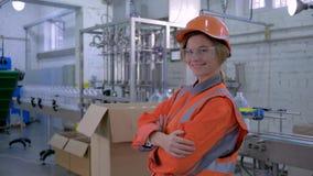Ritratto dell'ingegnere femminile sorridente felice nel casco e delle tute sul lavoro vicino alla linea del trasportatore archivi video