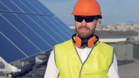 Ritratto dell'ingegnere Il lavoratore sorridente sta girando la sua testa e leggermente il sollevamento del suo elmetto protettiv archivi video
