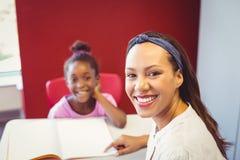 Ritratto dell'insegnante che aiuta una ragazza con il suo compito in aula Immagine Stock