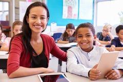 Ritratto dell'insegnante con il ragazzo della scuola elementare al suo scrittorio Immagini Stock