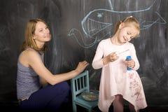 Ritratto dell'insegnante con l'allievo alla lavagna Immagine Stock