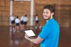 Ritratto dell'insegnante di sport che per mezzo della compressa digitale immagini stock libere da diritti