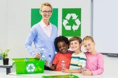 Ritratto dell'insegnante e dei bambini che stanno nell'aula Immagine Stock