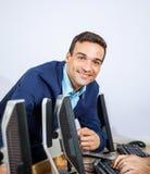 Ritratto dell'insegnante felice Assisting Senior Student al computer D Immagine Stock