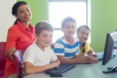 Ritratto dell'insegnante femminile sorridente con i bambini Fotografie Stock