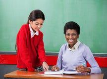 Ritratto dell'insegnante With Girl Pointing sul raccoglitore Immagini Stock