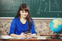 Ritratto dell'insegnante la bella giovane donna in un vestito blu si siede ad uno scrittorio con un globo sui precedenti di un bo Immagini Stock Libere da Diritti