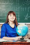 Ritratto dell'insegnante la bella giovane donna in un vestito blu si siede ad uno scrittorio con un globo sui precedenti di un bo Immagini Stock