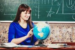 Ritratto dell'insegnante la bella giovane donna in un vestito blu si siede ad uno scrittorio con un globo sui precedenti di un bo Fotografia Stock Libera da Diritti