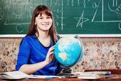 Ritratto dell'insegnante la bella giovane donna in un vestito blu si siede ad uno scrittorio con un globo sui precedenti di un bo Immagine Stock