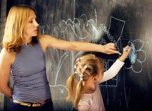 Ritratto dell'insegnante maturo della donna con piccola scrittura bionda sveglia dell'allievo della ragazza sulla lavagna insieme Fotografia Stock Libera da Diritti