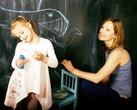 Ritratto dell'insegnante maturo della donna con piccola scrittura bionda sveglia dell'allievo della ragazza sulla lavagna insieme Fotografia Stock