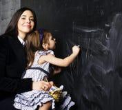 Ritratto dell'insegnante maturo della donna con piccola scrittura bionda sveglia dell'allievo della ragazza sulla lavagna insieme Fotografie Stock