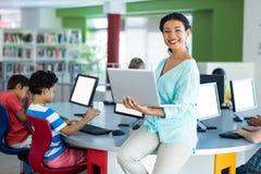Ritratto dell'insegnante sorridente che per mezzo del computer portatile Immagine Stock
