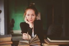 ritratto dell'interno dei libri felici di apprendimento o di lettura della donna dello studente della testarossa immagini stock libere da diritti