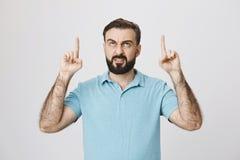 Ritratto dell'interno del maschio barbuto europeo arrabbiato che indica su con i dito indice ed il sorriso triste, sopra fondo gr Fotografia Stock Libera da Diritti