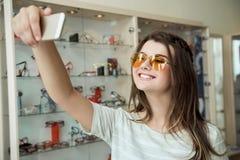 Ritratto dell'interno di bella giovane donna nel deposito dell'ottico, paio nuovo d'acquisto degli occhiali da sole per protegger Immagine Stock