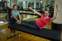 Ritratto dell'istruttore femminile che assiste donna con l'allungamento dell'esercizio sul riformatore Immagini Stock