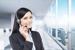 Ritratto dell'operatore allegro sorridente del telefono di sostegno in cuffia avricolare Immagini Stock
