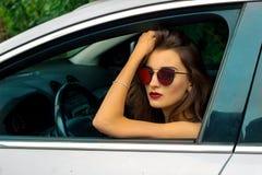 Ritratto dell'ragazze eleganti con i vetri nell'automobile Fotografia Stock