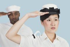 Ritratto dell'ufficiale serio della marina statunitense e del marinaio femminili del maschio che salutano sopra il fondo blu-chiar Fotografia Stock