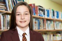 Ritratto dell'uniforme scolastico d'uso della ragazza in biblioteca Fotografia Stock