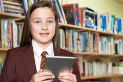 Ritratto dell'uniforme scolastico d'uso della ragazza facendo uso della compressa di Digital dentro Fotografie Stock Libere da Diritti