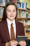 Ritratto dell'uniforme scolastico d'uso della ragazza facendo uso della compressa di Digital dentro Immagine Stock Libera da Diritti
