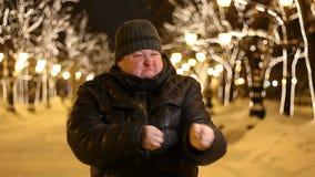 Ritratto dell'uomo adulto del gamer, che imita i colpi di arma di fuoco all'aperto durante la notte fredda dell'inverno stock footage
