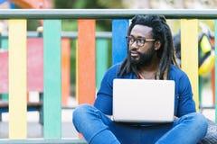 Ritratto dell'uomo africano che si siede fuori con il computer portatile Fotografia Stock Libera da Diritti