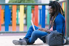 Ritratto dell'uomo africano che si siede fuori con il computer portatile Immagini Stock Libere da Diritti